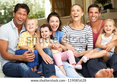 Two Families Sitting Outside House - stock photo