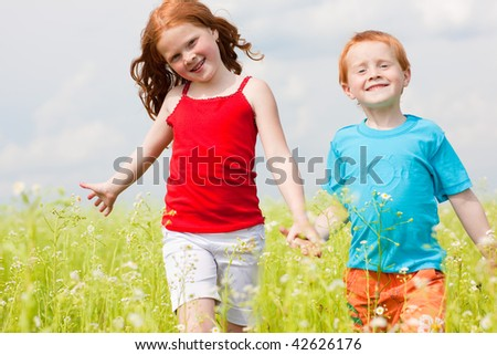 Two fan children playing on the field - stock photo