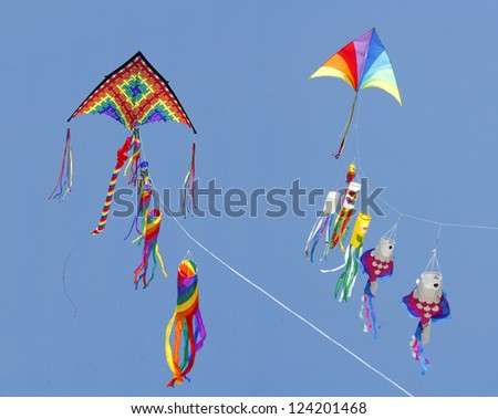Two Fancy Kites Flying in a Bright Blue Sky - stock photo