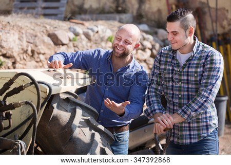 Two farmers talking near the agricultural machinery at the shed  - stock photo