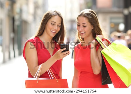Two fashion colorful shoppers with bags shopping with a smart phone in the street - stock photo