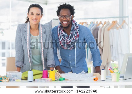 Two fashion designers smiling and looking at camera - stock photo