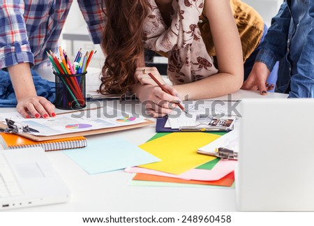 Two fashion designers working together at the desk - stock photo