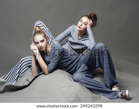 two fashion model girl posing on gray background