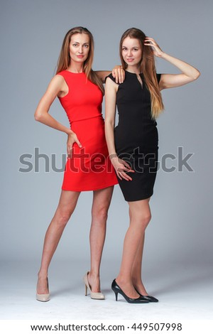 Two fashion models posing in studio on black background