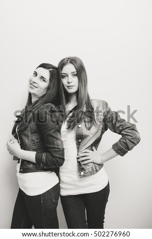 Two fashion young women posing in studio. Jeans jackets. Black and white image.
