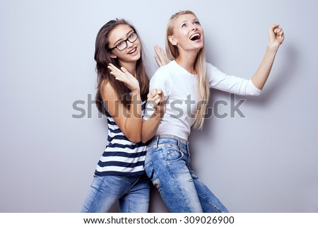 Two fashionable beautiful young girls posing, smiling, wearing jeans. Girls having fun. Studio shot. - stock photo