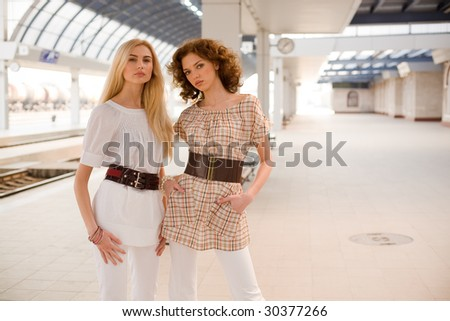 Two fashionable girls on railway station