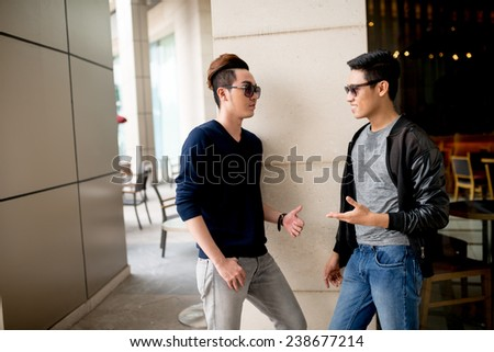 Two fashionable male friends chatting - stock photo
