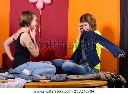 Two fashionable teenage girls choosing clothes.