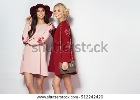 Two fashionable women in nice dresses. Fashion autumn photo