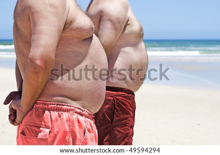 Two fat men on a beach - stock photo