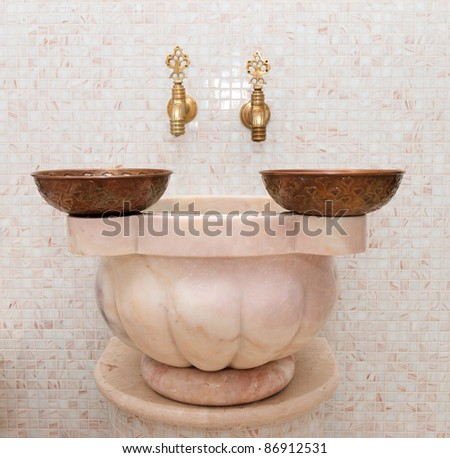 Two faucets and two copper bowl in turkish bath - stock photo