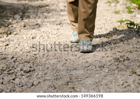 Two feet are hiking on a stony way in Tirol - stock photo