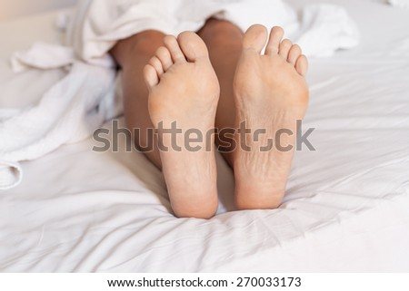 Two feet in a white bed