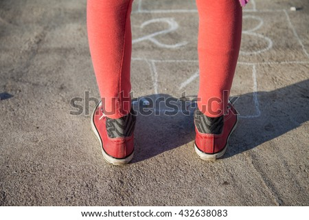 Two feet in red sneakersstanding ready to start playing the game of hopscotch