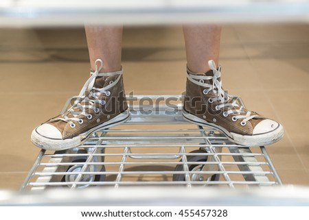 two feet with red shoes on supermarket trolley  - stock photo