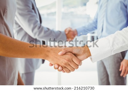 Two fellow employees shaking hands at work - stock photo