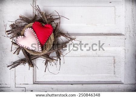 Two felt hearts in a nest on a antique wooden background - stock photo