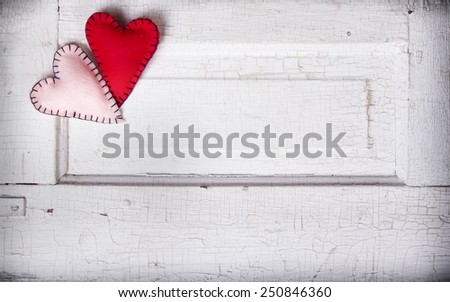 Two felt hearts on an antique wooden background - stock photo