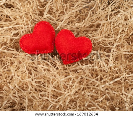 Two felt red hearts on the sawdust.