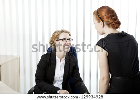 Two female business colleagues having a chat and laughing together as they share a private moment during an informal meeting in the office - stock photo