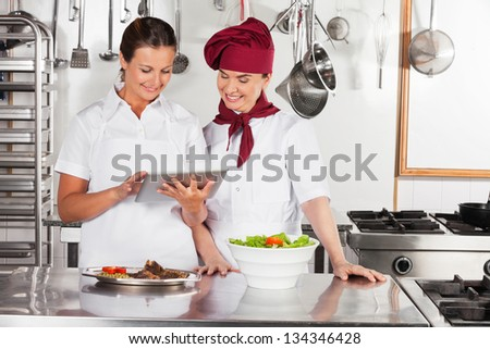 Two female chefs using digital tablet in commercial kitchen - stock photo