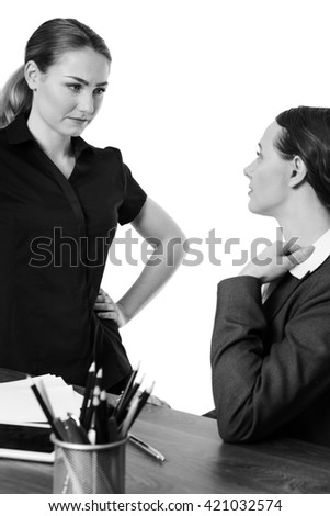 two female co-workers in an office.  One sitting at a desk wearing a suit and another standing opposite, having a conversation.