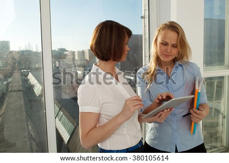 Two female colleagues standing at window in sunlight. Blonde woman typing on tablet.