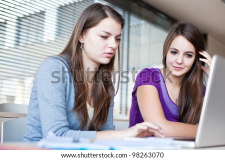 Two female college students working on a laptop computer during class (color toned image) - stock photo