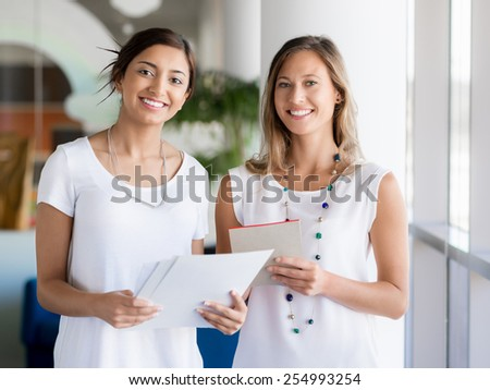 Two female collegues standing next to each other in an office - stock photo