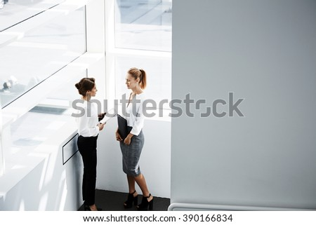Two female confident business worker having conversation during work break, while are standing in hallway company near wall with copy space for your advertising text message or promotional content - stock photo