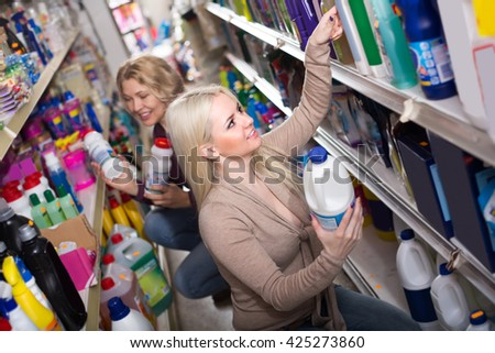 Two female customers choosing detergents for house in the shopping mall