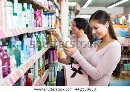 Two female customers selecting haircare products in drugstore. Selective focus