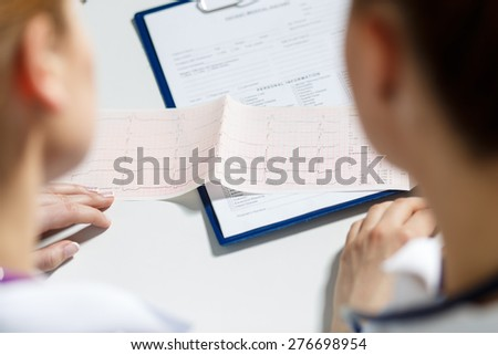 Two female doctors examining patient cardiogram chart. Professional conversation, council of cardiologists. Working conference. Medical concept - stock photo