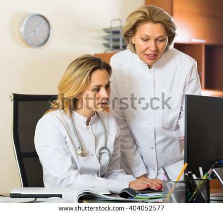 Two female doctors in white overalls working on computer at cabinet