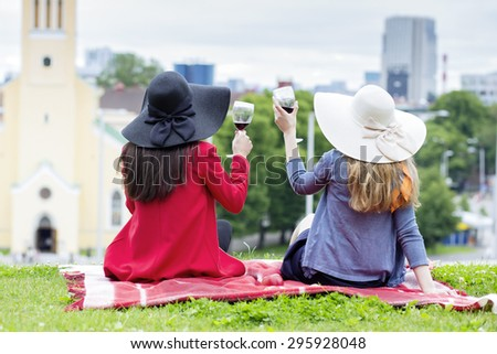 Two female drinking together red wine outdoors