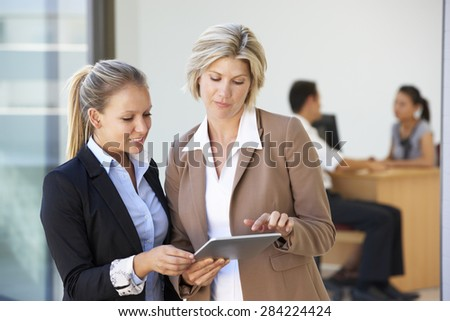 Two Female Executives Looking At Tablet Computer With Office Meeting In Background - stock photo