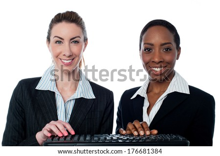 Two female executives typing on keyboard - stock photo