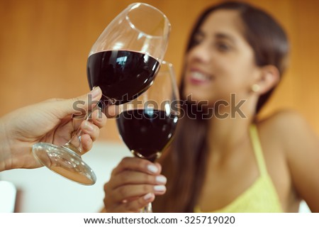 Two female friends at home, relaxing with a glass of red wine. The girls smile and celebrate making a toast. Focus on foreground