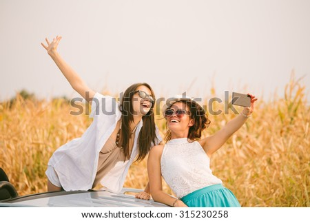 Two female friends beside cabriolet taking selfies with smartphone - stock photo