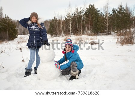 two female friends building a snowman. funny girls on a walk in the winter outdoors