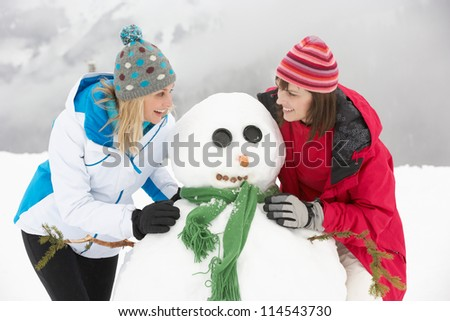 Two Female Friends Building Snowman On Ski Holiday In Mountains - stock photo