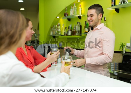 Two female friends chatting and drinking wine at the bar - stock photo
