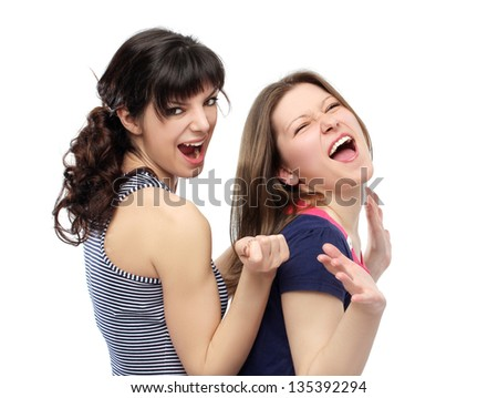 Two female friends dancing and singing.White background - stock photo