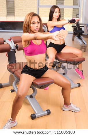 two female friends exercising in the gym