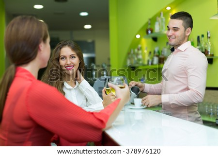 Two female friends flirting with a handsome barman - stock photo