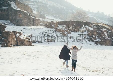 Two female friends having fun on winter day in park  - stock photo