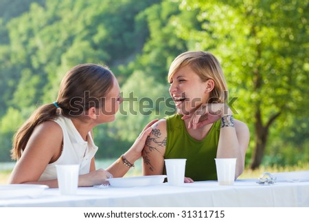 two female friends having picnic outdoors and laughing