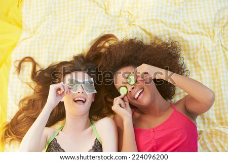 Two Female Friends Lying On Bed Using Beauty Treatments - stock photo